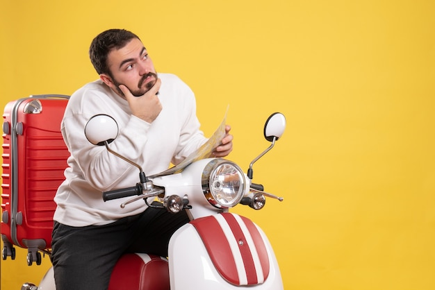 Front view of young thoughtful man sitting on motorcycle with suitcase on it holding map on isolated yellow background