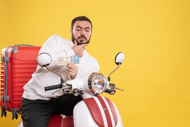 Front view of young thoughtful travelling man sitting on motorcycle with suitcase on it holding ticket on isolated yellow background