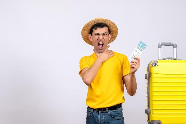 항공 티켓을 들고 노란색 가방 근처에 서있는 노란색 티셔츠에 전면보기 젊은 관광