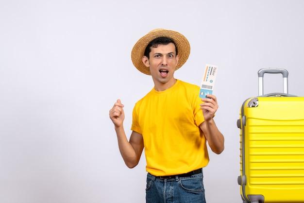 티켓을 들고 노란색 가방 근처에 서있는 노란색 티셔츠에 전면보기 젊은 관광