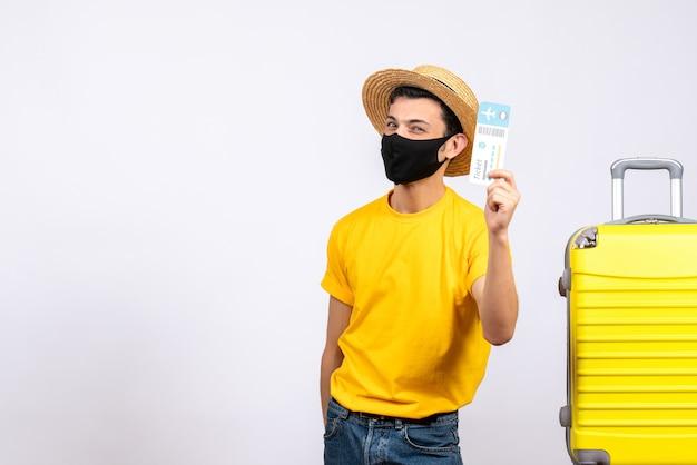 여행 티켓을 들고 노란색 가방 근처에 서있는 노란색 티셔츠에 전면보기 젊은 관광