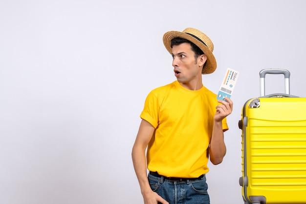 왼쪽 티켓을 들고 노란색 가방 근처에 서있는 노란색 티셔츠에 전면보기 젊은 관광