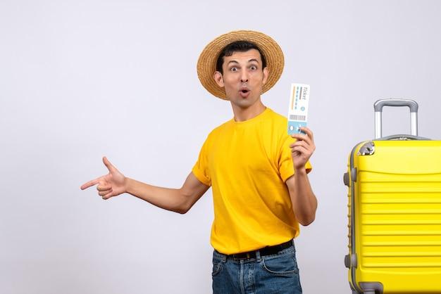 왼쪽을 가리키는 노란색 가방 근처에 서있는 노란색 티셔츠에 전면보기 젊은 관광
