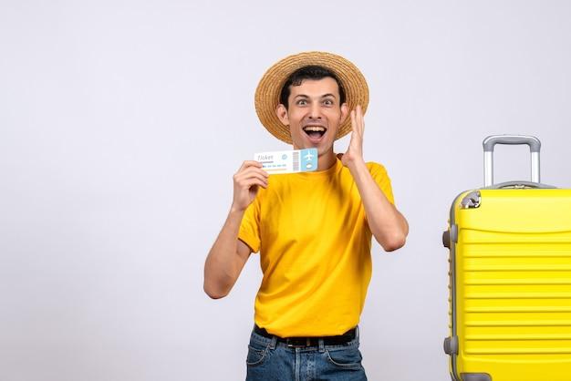 티켓을 들고 그의 감정을 표현하는 노란색 가방 근처에 서있는 전면보기 젊은 관광객