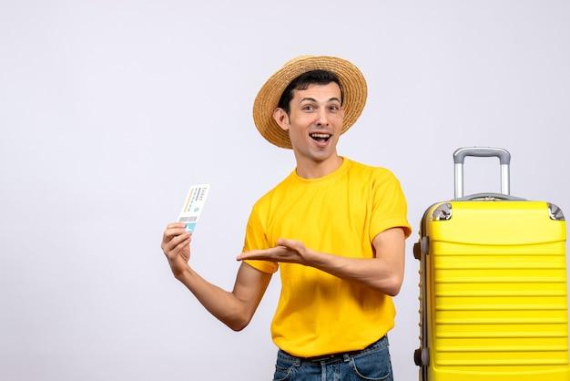 항공 티켓을 들고 노란색 가방 근처에 서 전면보기 젊은 관광객
