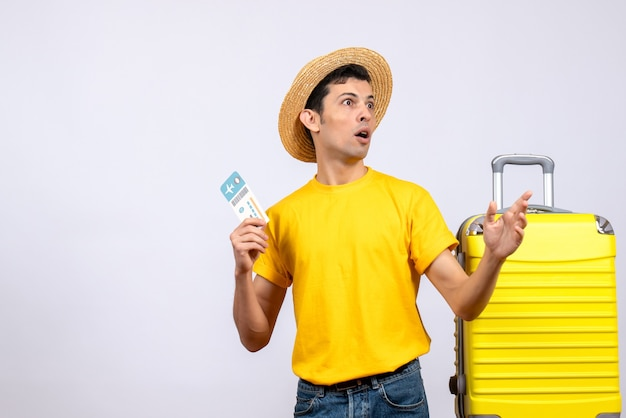 Front view young tourist standing near yellow suitcase holding ticket looking at something