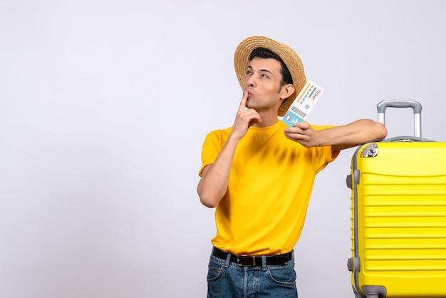 뭔가에 대해 생각하는 티켓을 들고 노란색 가방 근처에 서 전면보기 젊은 관광객