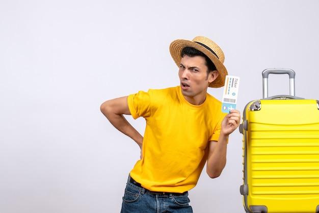 티켓을 들고 노란색 가방 근처에 서 전면보기 젊은 관광