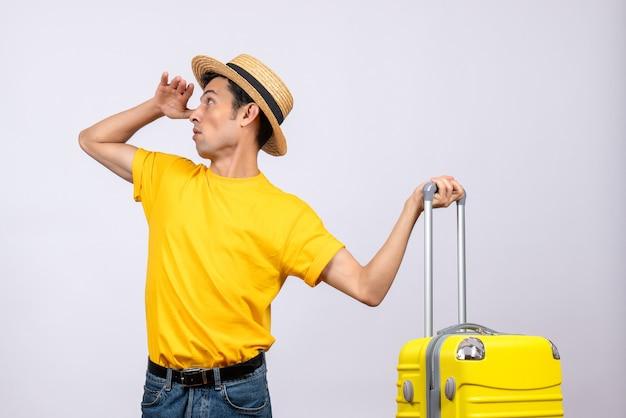 뭔가 들고 가방을 찾고 노란색 가방 근처에 서 전면보기 젊은 관광