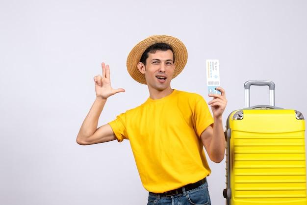 티켓을 들고 손가락 총을 만드는 노란색 가방 근처에 서 전면보기 젊은 관광객