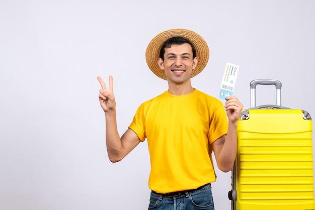 Вид спереди молодой турист, стоящий возле желтого чемодана, делающий знак v, держащий авиабилет