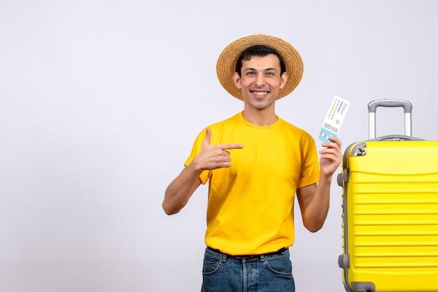항공 티켓을 가리키는 노란색 가방 근처에 서 전면보기 젊은 관광객