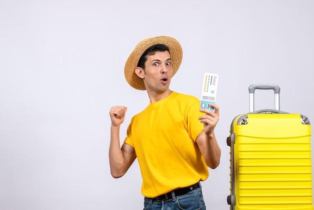 티켓을 들고 뒤에 가리키는 노란색 가방 근처에 서 전면보기 젊은 관광객