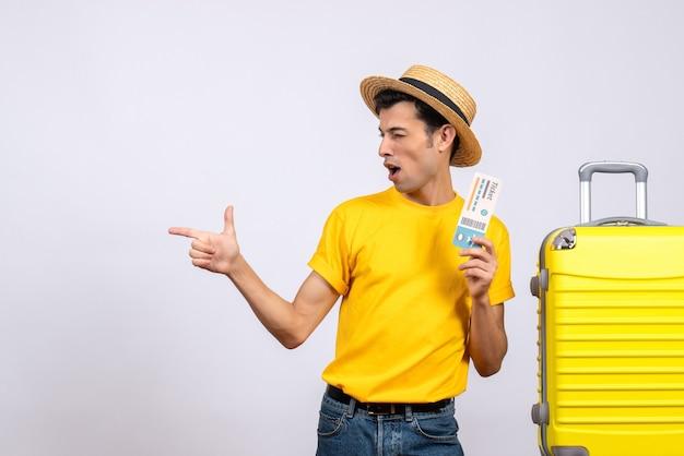 왼쪽 티켓을 들고 가리키는 노란색 가방 근처에 서 전면보기 젊은 관광객