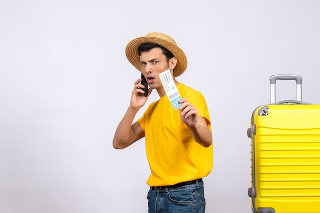 항공 티켓을 들고 전화 통화 노란색 가방 근처에 서 전면보기 젊은 관광객