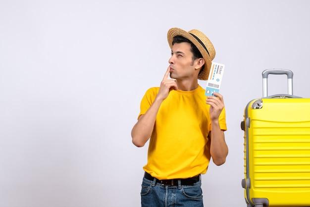 뭔가 대해 생각하는 노란색 가방 근처에 서 전면보기 젊은 관광