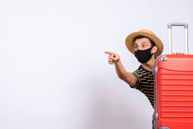 Giovane turista di vista frontale con maschera nera che si nasconde dietro il dito puntato della valigia rossa qualcosa