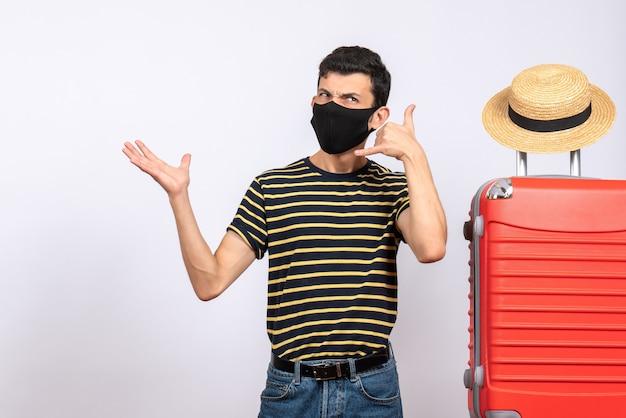 Giovane turista di vista frontale con la maschera nera che sta vicino al segnale di chiamata della valigia rossa