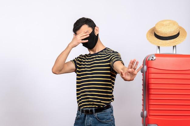 手で目を閉じて赤いスーツケースの近くに立っている黒いマスクを持つ正面図若い観光客