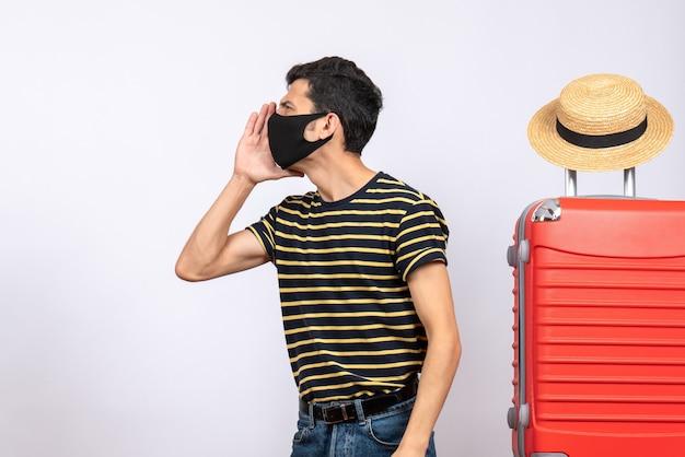 Вид спереди молодой турист с черной маской, стоящий возле красного чемодана и кричащий на кого-то