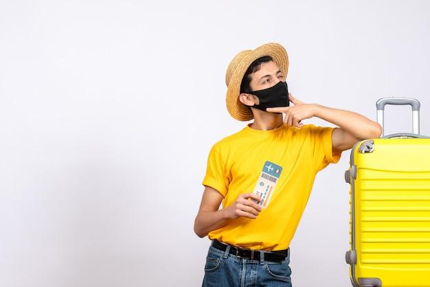 旅行チケットを保持している黄色のスーツケースの近くに立っている麦わら帽子と正面図