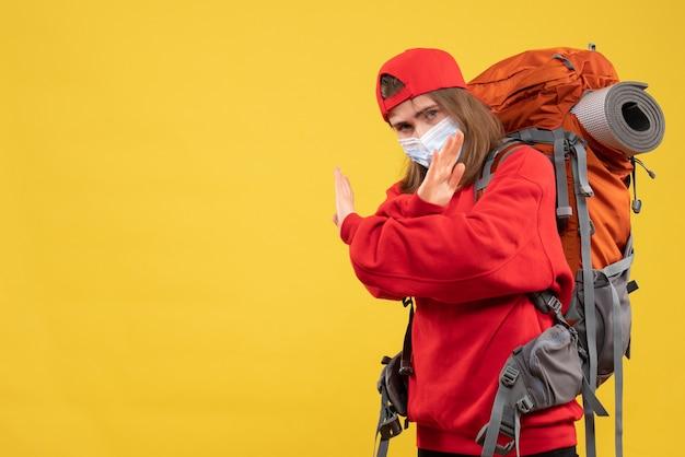 観光バックパックとマスク交差点の手を持つ若い観光客の正面図