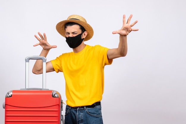 黄色のtシャツと赤いスーツケースと正面図の若い観光客