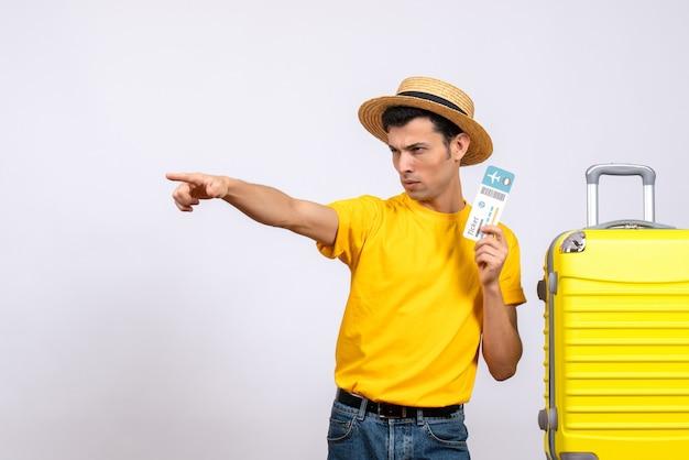 Giovane turista di vista frontale in maglietta gialla che sta vicino alla valigia gialla che indica qualcosa