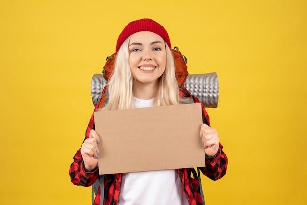 黄色の壁に立っている段ボールを保持している赤い帽子の正面図若い旅行の女の子