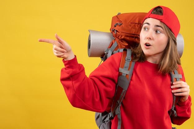Вид спереди молодая путешественница в красной кепке с рюкзаком, указывающим налево
