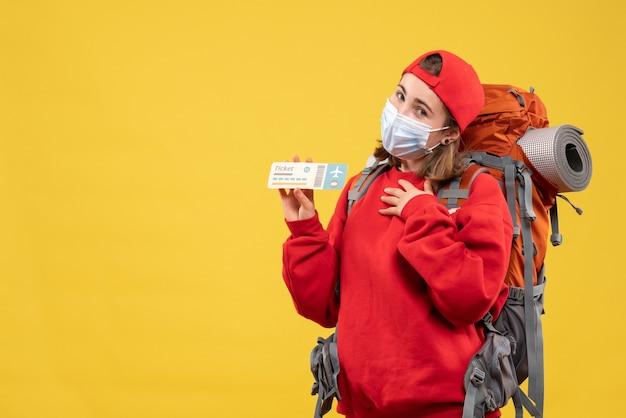 Вид спереди молодая путешественница с рюкзаком и маской, держащая билет на самолет