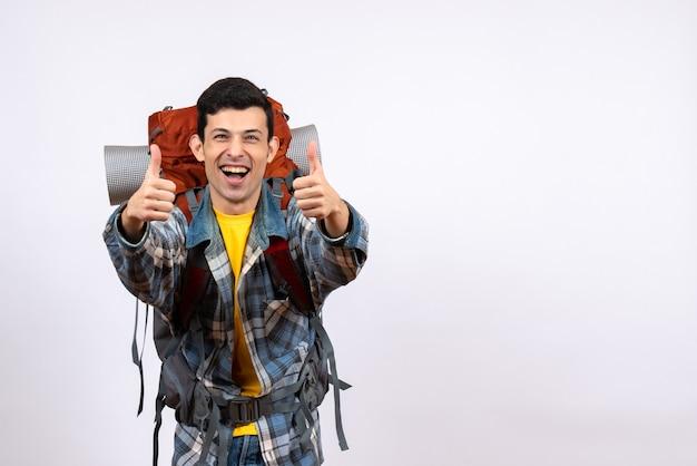 親指をあきらめるバックパックと正面図の若い旅行者の男性