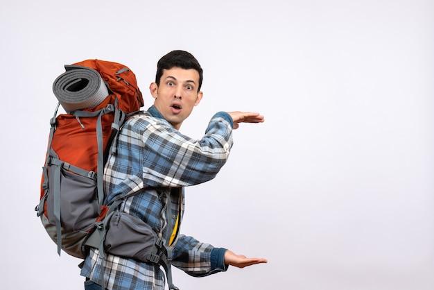 手でサイズを示すバックパックと正面図の若い旅行者の男性