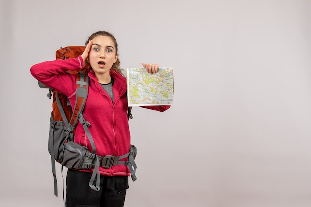 Front view young traveller in confusion with big backpack holding map