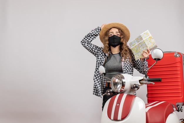 Vista frontale giovane viaggiatrice con maschera nera che tiene mappa in piedi vicino al motorino rosso red