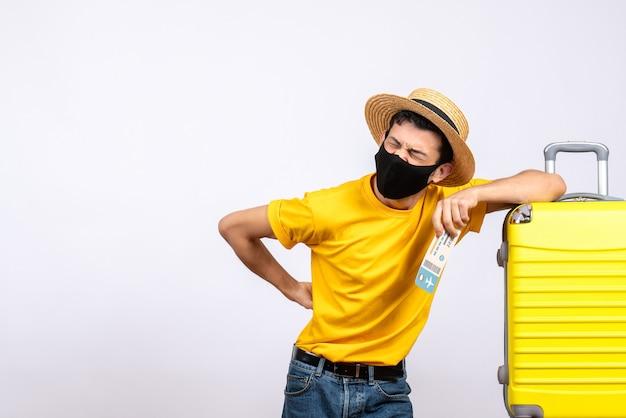 항공 티켓을 들고 노란색 가방 근처에 서있는 노란색 티셔츠에 전면보기 젊은 여행자
