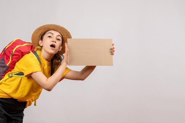 Vista frontale giovane viaggiatore con zaino che tiene cartone