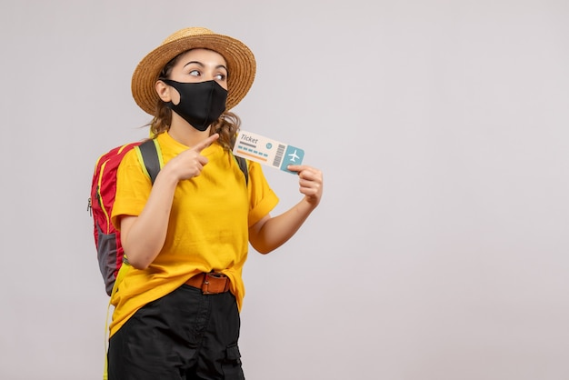 Giovane viaggiatore di vista frontale con lo zaino che sostiene il biglietto che indica a destra