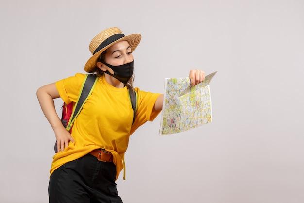 バックパックを持った若い旅行者の正面図が腰に手を当てて地図を見て