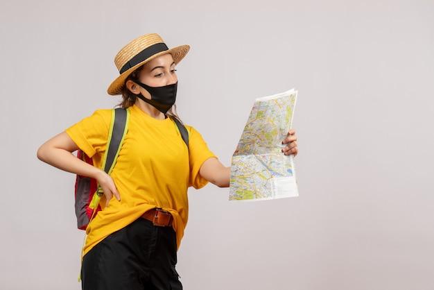 Vista frontale giovane viaggiatore con zaino che guarda la mappa mettendo la mano su una vita