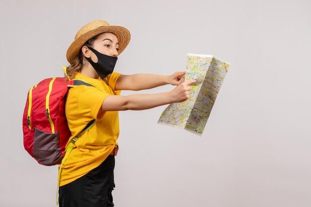 Vista frontale giovane viaggiatore con zaino guardando la mappa