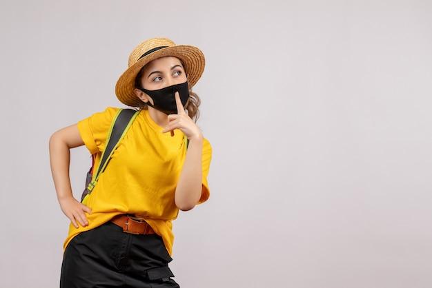 Вид спереди молодой путешественник с рюкзаком, делая знак тишины