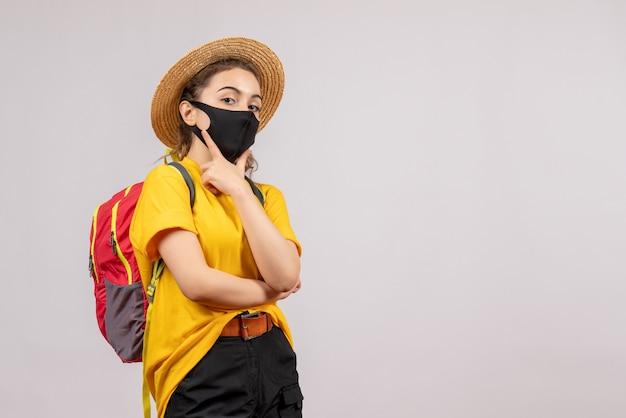 Giovane viaggiatore di vista frontale con lo zaino che mette la mano sul suo mento