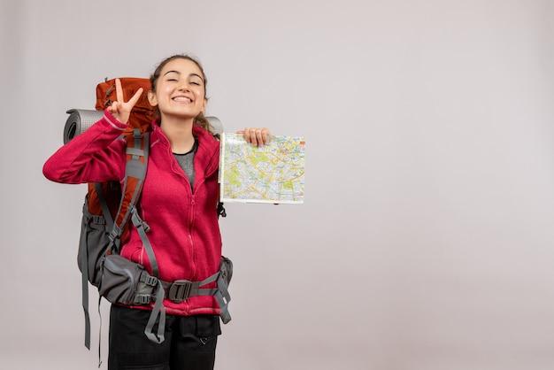 Okサインを身振りで示す地図を持った大きなバックパックを持つ正面の若い旅行者