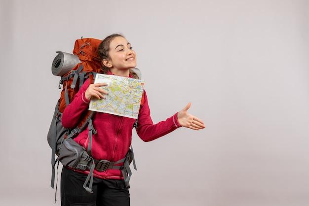 手を与える地図を持った大きなバックパックを持つ正面の若い旅行者