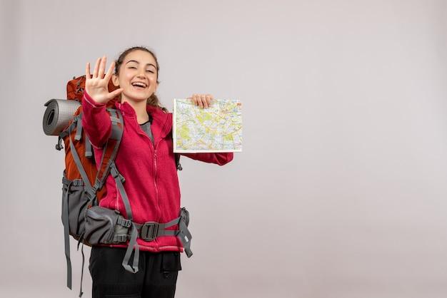 Vista frontale giovane viaggiatore con un grande zaino con in mano una mappa che saluta qualcuno