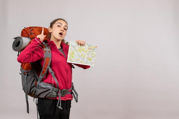 地図を人差し指で持つ大きなバックパックを持つ若い旅行者の正面図