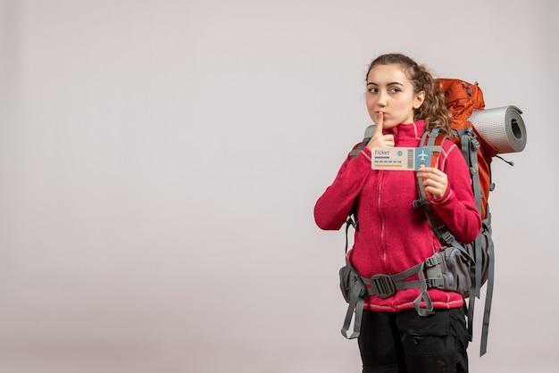 Vista frontale giovane viaggiatore con grande zaino che sorregge il biglietto di viaggio mettendo il dito sulla bocca