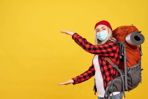 黄色の壁に手でサイズを示す彼女のバックパックと正面図若い旅行者
