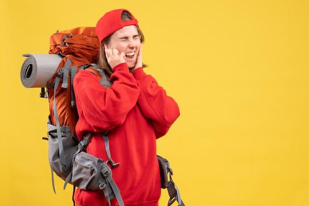 耳を閉じて叫んでいる赤いバックパックの正面図若い旅行者の女性